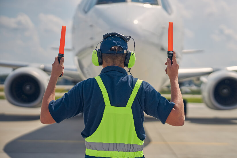 6 photodune 9OI6cy5h marshaller in the safety overalls signaling the pilot tiny